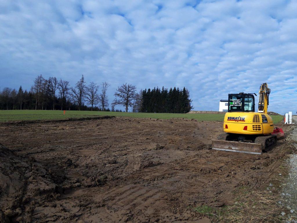 Unser Bagger im Einsatz. Man sieht die Baggerungen und Erdarbeiten. Im Hintergrud ein bewölkter Himmel und einige Bäume die hinter dem Feld stehen.