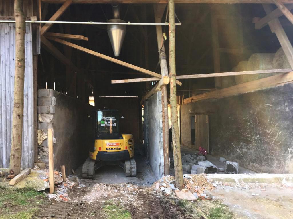 BAgger beim Abriss in einer Scheune. Holzpfosten stehen noch.