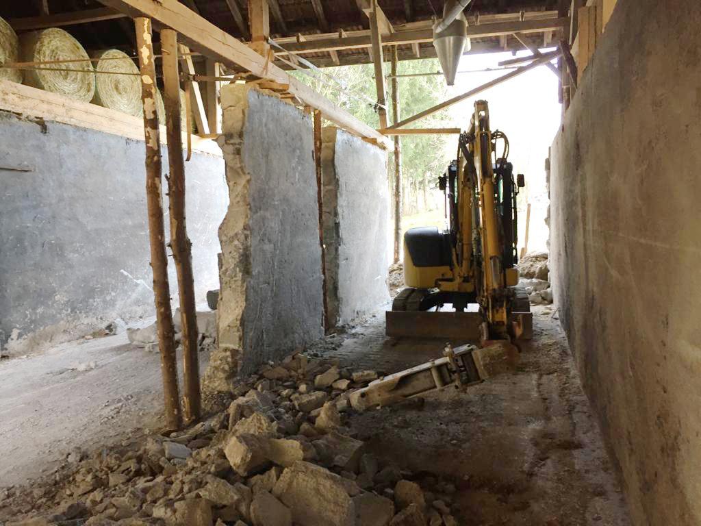 BAgger beim Abriss in einer Scheune. Holzpfosten stehen noch. Die Mauer wird vom Bagger eingerissen.