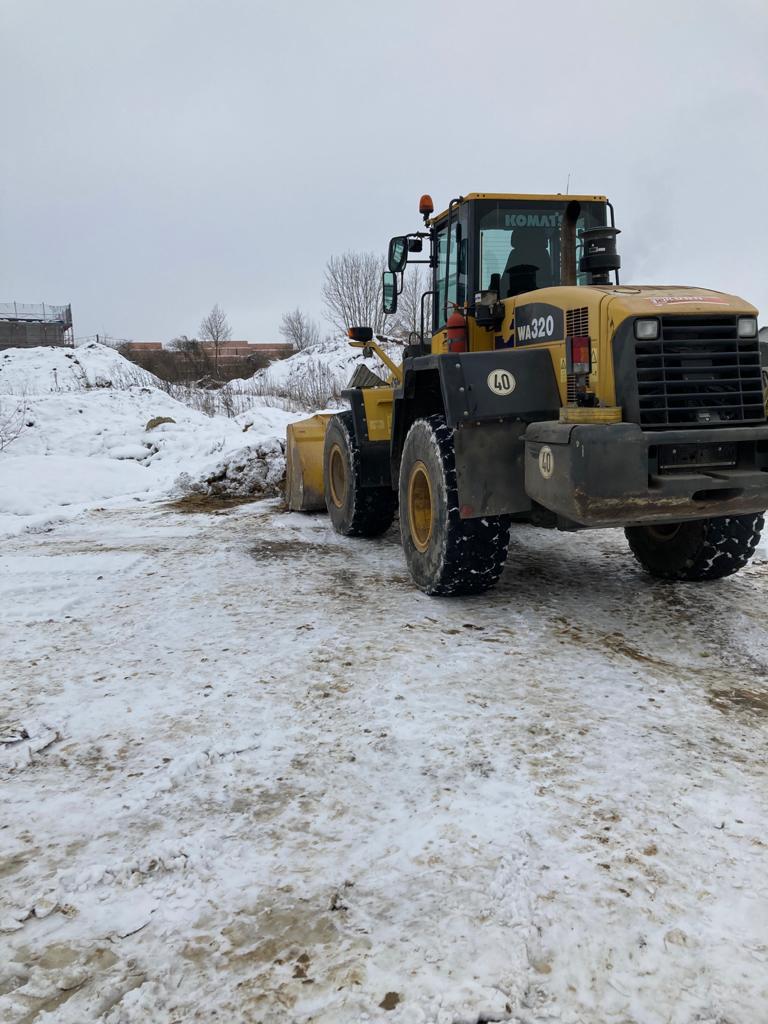 Der gelbe Radlader im Einsatz bei Schnee und Kälte.