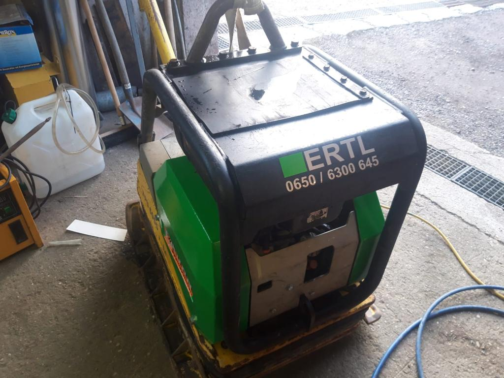 Die grüne Rüttelplatte trägt unser Ertl Logo und steht in der Lagerhalle.