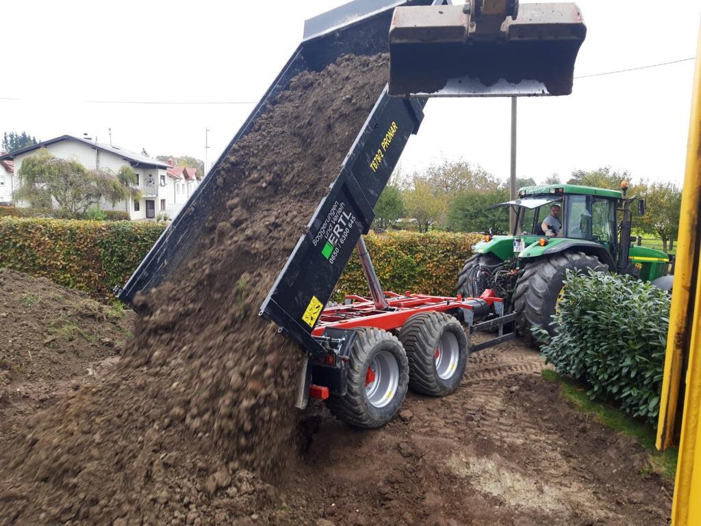 Der grüne Traktor mit Pronar Kipper beim Abladen der Erde.